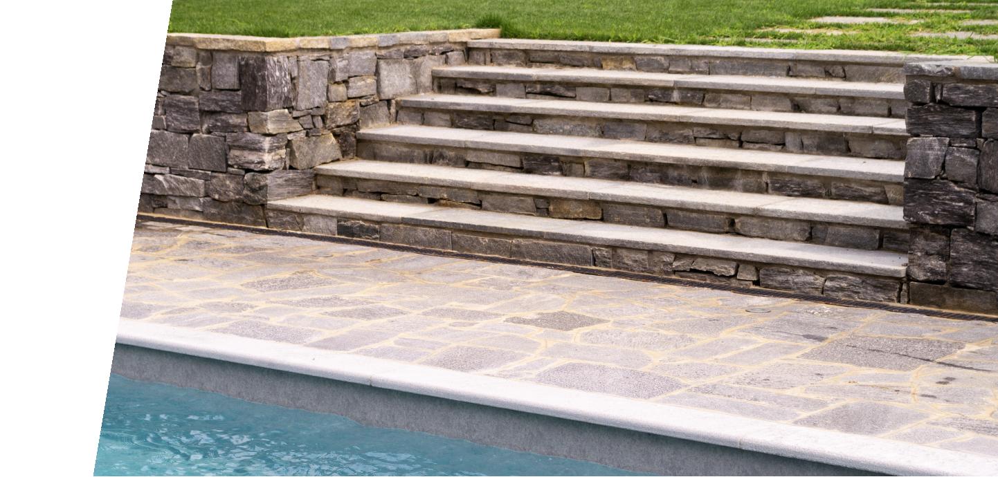 Pavimentazione in pietra, con scala e rivestimenti a bordo piscina